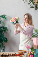 Picture of florist holding bouquet in hands at table with marmalade, marshmallow, boxes, paper