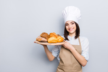 White uniform high hat industry manufacture people eating nutrition concept. Portrait of charming woman carrying wooden round tray full of yummy palatable nourishing bread isolated on gray background