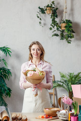 Photo of florist in apron with bouquet of flowers with kraft paper on background of indoor plants