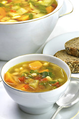 plant based organic vegetable soup in a bone china white bowl showing a lager serving dish in the background  room for copy space