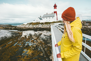 Woman sightseeing Norway lighthouse landscape Travel Lifestyle concept adventure tourist at vacations outdoor girl wearing yellow raincoat standing alone