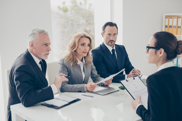 Portrait of young attractive woman in glasses having job interview with three stylish business persons in financial company, asking, answering the questions, holding cv in hands