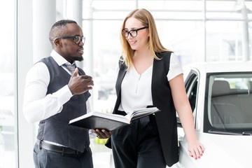 African man stands in glasses talking to a customer buying a new car in the showroom