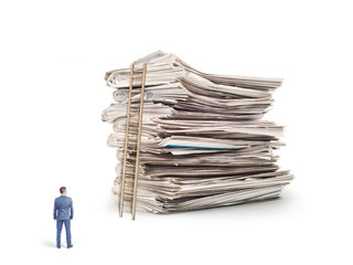 The concept of learning. A man in a business suit is standing in front of a stack of newspapers isolated on a white background.