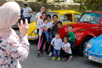A woman takes a pictures of her children posing in front of vintage cars in Amman
