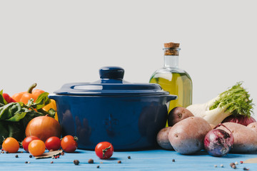 pan with ripe organic vegetables and olive oil on blue table
