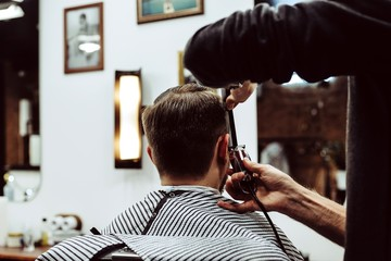 Male hairdresser cuts a man's hair with clippers at the Barber shop, the concept of the 80s