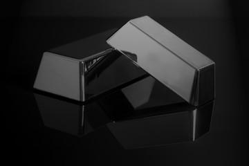 silver bullion bars on black background