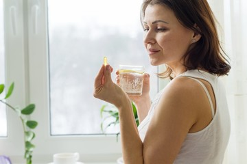 Woman takes pill with omega-3 and holding a glass of fresh water with lemon. Picture of the house, in the morning near the window.