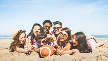 Group of multiracial happy friends having fun playing sport beach games - International concept of summer joy and multicultural friendship together - Young people millennials on warm vintage filter