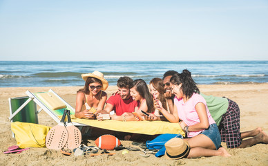 Group of multiracial friends having fun together with smartphone - Young people social networking with mobile smart phone in sunny day - Technology concept in summer beach everyday lifestyle