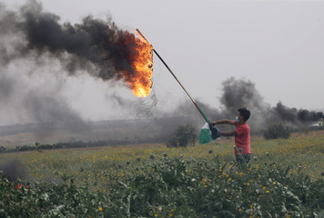 Palestinian demonstrator holds a burning tire during clashes with Israeli troops near the border with Israel, in the southern Gaza Strip