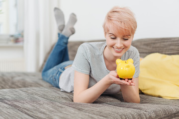 Cheerful young woman holding her piggy bank