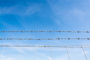 Barbed wire fence against blue sky with thin cloud - abstract background - 1