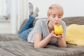 Pretty young blond woman kissing her piggy bank