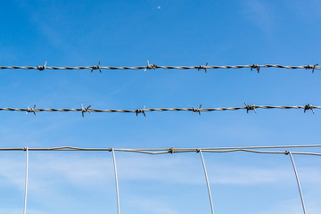 Barbed wire fence against blue sky with thin cloud - abstract background - 2