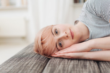 Thoughtful woman lying resting on a couch