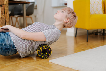 Woman exercising her back with foam roller