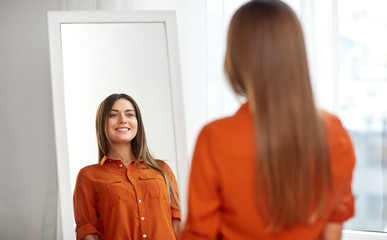 wardrobe, fashion, style and people concept - happy woman in orange shirt looking at mirror reflection at home or clothing store dressing room Wall mural