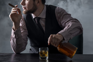A man sits at a table and pours into a glass from a bottle of whiskey