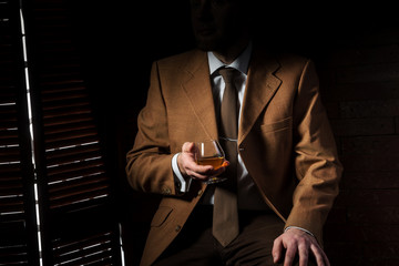 Man in suit with cognac glass in luxury interior. No face