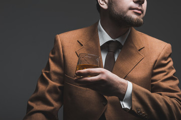 Handsome bearded businessman is drinking expensive whisky closeup. tonned image