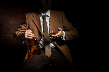 Man in suit with cognac glass and bottle in luxury interior. without face