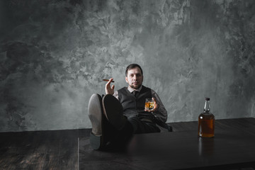 Attractive man with cigar and whiskey rests. Legs on the table
