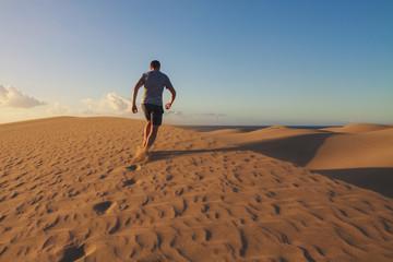 Man is running on sand dunes in Maspalomas.