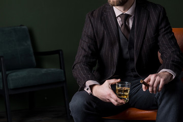 Man in expensive suit is sitting on the leather armchair and drinking whiskey. No face