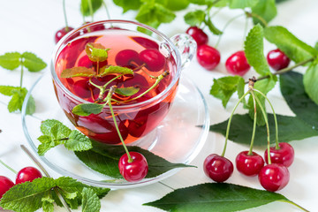 esh fruit cherry drink in transparent glass cup surrounded by cherries