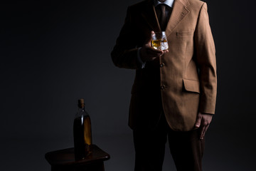 Man in jacket stands near table with bottle  of whiskey and glass. No face