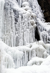 Frozen waterfall with icicles and snow near Bad Harzburg in the fir forests and spruce forests along the main road to Braunlage in the Harz mountains.