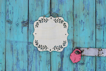 Blank wooden sign with floral border hanging on rustic antique teal blue wood door with heart-shaped lock