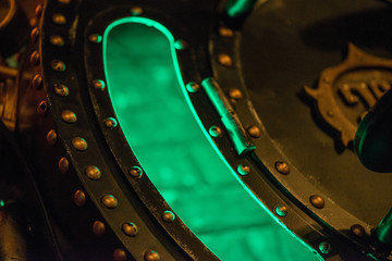 Abstract macro shot of vintage steam punk bronze home decor with green light