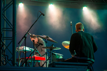 Shot of a man playing drums on stage during music festival in summer. Band performing their songs. Live concert of electronic music at night. Colorful lights and lasers