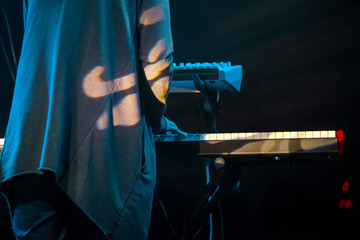 Male musician plays a musical instrument on the stage. Artist playing on the keyboard synthesizer piano keys. Live concert of electronic music at night in summer festival. Colorful, abstract lights.