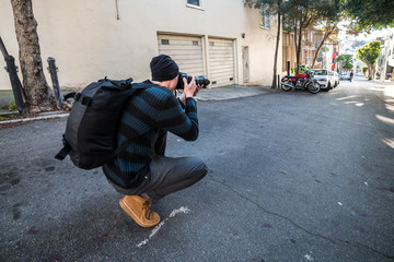 Photographer taking pictures during his travel on city streets