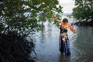 A young beautiful woman walks in a mangrove trees. Inside a mangrove forest Thailand