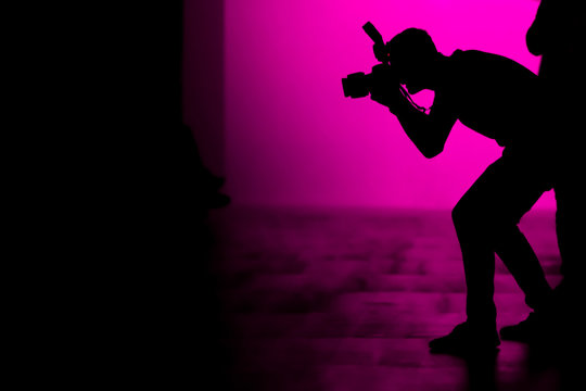 Silhouette of a photographer taking photographs of celebrities on the fashion show.
