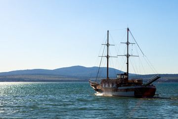 The ship with the masts of the Black sea mountains in the background in hotelskih sunset