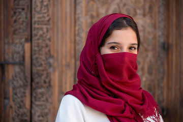 Portrait of young muslim woman with red hijab headscarf over her face