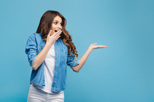 Beautiful young woman in yellow sweater posing on blue background. Attractive woman pointing fingers to the right with cheerful and happy expression. Copy space.