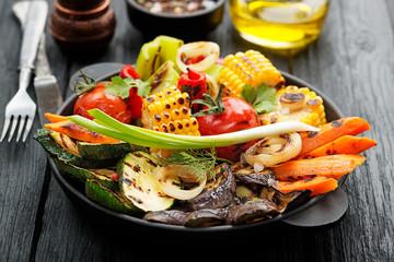 Delicious grilled vegetables on black  wooden background.