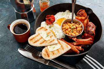 Traditional full English breakfast with fried eggs, sausages, beans, grilled tomatoes and bacon.