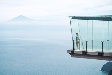 Woman looking at view while standing in Mirador de Abrante against sea and mountains during foggy weather