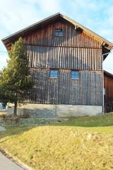Holzfassade eines Bauernhauses im hügeligen Alpenvorland im Frühling, Allgäu