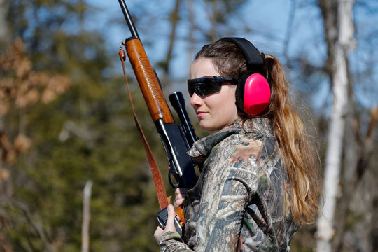 Woman holding a gun and wearing ear muffs.