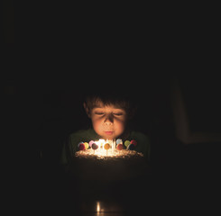 Boy blowing birthday candles on cake in darkroom
