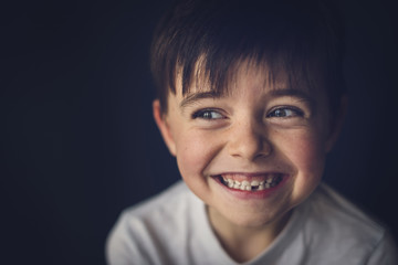 Cheerful boy with gap toothed looking away in darkroom